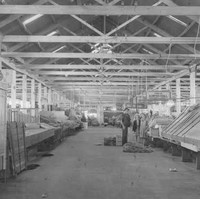 Image: A man and two women stand among produce stalls in a large warehouse