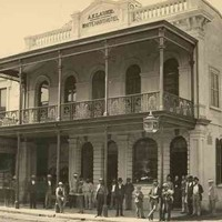 "Image: a group of men, a woman and a boy in 1870s attire stand outside a two storey hotel with a balcony, arched windows, and a parapet sign which reads ""A.KLAUER WHITE HEART HOTEL"""