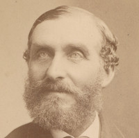 Image: A photographic head-and-shoulders portrait of a bearded middle-aged man in a suit with bowtie