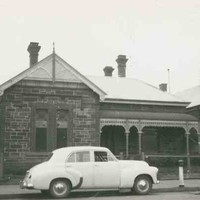 Image: a white 1950s era car is parked outside a small bluestone cottage with a verandah