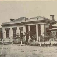 Image: a single storey building with grand columned portico under which figures can be seen standing. A garden can be seen behind a fence to the right of the building.