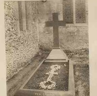 Image: Photograph of cross shaped headstone beside a church