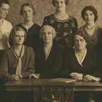 Image: A group of women are gathered around a table. The front row is seated, while those in the back row stand