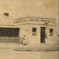 """Image: a single storey cottage with pitched roof and verandah situated behind a picket fence adjoins a small square, flat roofed building with a central door flanked by two small windows. The square building has signs reading: """"Railway Hotel"""""""