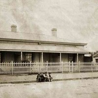 Image: A group of boys are sitting on the kerb in front of terraced cottages with a white picket fence. Geese can be seen near a tumbledown building on the right