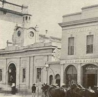 Image: A rectangular single-storey building with central clock tower and cupola is located next to a row of rectangular buildings. A horse-drawn carriage stands in the dirt street in front of these buildings