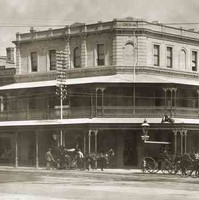 Image: a three storey corner hotel with a protruding balcony on the second floor which also forms a verandah. Horse drawn vehicles pass on the street outside.