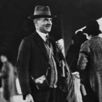 Image: A man in a hat and suit stands on a platform at a railway station. He is carrying a wooden box and several leather equipment satchels