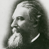 Image: The head and shoulders of a middle-aged man with long hair and a large goatee in profile. The left side of the man's face is visible