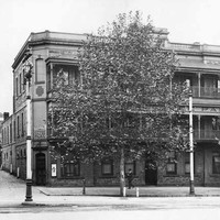 Image: a large tree obscures the view of a three storey stone building on the corner of a wide street and small alley. The building has balconies on its second and third floor and a corner door at street level.