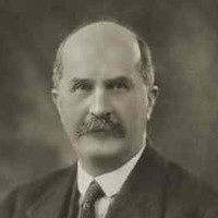 Image: A photographic portrait of a balding, moustachioed middle-aged man wearing a suit and tie