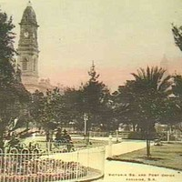 Image: Early coloured photograph of formal gardens with the Post Office tower visible in the background