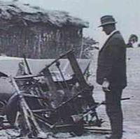 Image: Two men in suits and hats examine a section of aircraft wreckage. A stone house is visible in the immediate background