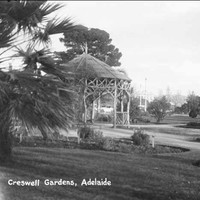 Image: Black and white photograph of a rustic wooden rotunda situated in public gardens. Indistinct figures wander along the garden paths in the middle-ground while buildings can be seen in the distance.