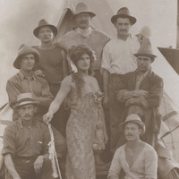 Image: group of men with centre man dressed up as a woman