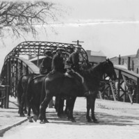 Image: Several men on horseback form two ranks in front of an iron bridge