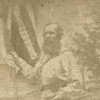 Image: Photograph of bearded man standing in front of a painted background of a beach. He stands in three quarter profile, legs crossed, and holds a flag in his right hand. His hat sits on the ground in front of him.