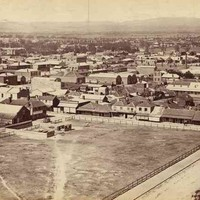 Image: A large open fenced paddock is surrounded by several dirt streets, buildings and houses