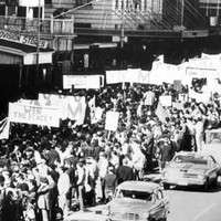 Image: a large group of people holding protest signs against the Vietnam War march down a city street