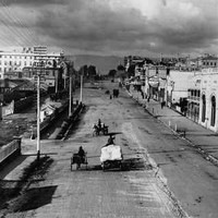 Image: dark clouds hang over a wide dirt city street which is lined with a variety of buildings from single storey tin sheds to large stone constructions of up to six storeys. Travelling down the road are a range of horse drawn vehicles.