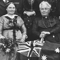Group of women sitting down in foreground with flag, women standing in background