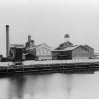Image: A complex of multi-storey brick buildings and large, corrugated metal-clad warehouses fronted by a river. A large brick chimney is visible at one end of the complex