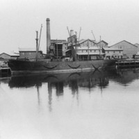 Image: A complex of multi-storey brick buildings and large, corrugated metal-clad warehouses fronted by a river. A large brick chimney is visible at one end of the complex, and a hulk is moored against its wharf