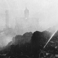 Image: A brick chimney and a few brick multi-storey buildings are shrouded in smoke from a fire. The burning sugar stock is visible in the foreground