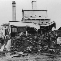 Image: Destroyed and partially-destroyed buildings are visible behind a large, burnt pile gunny sacks interspersed with twisted sheets of corrugated metal