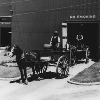 Image: Horse-drawn carts containing bags of sugar travel into a large corrugated metal-clad warehouse, while empty carts are transported out of another
