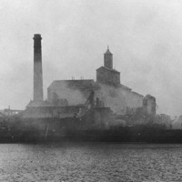 Image: A brick chimney and a few brick multi-storey buildings are shrouded in smoke from a fire. Other burned out structures are visible nearby