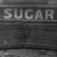 Image: A brick archway with the words 'Glanville Sugar Refinery' painted at its top is visible in front of a pile of burned, collapsed corrugated metal sheeting