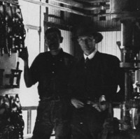 Image: Two men in 1920s attire stand inside a cavernous warehouse next to a large electrical switchboard