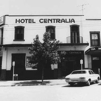 Image: a two storey corner hotel, painted white with dark windows and doors and a flat roof. Small, round balconetes protrude from some of the upper floor openings. 1980s era cars are parked on the street outside.