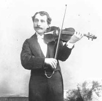 Image: A young moustachioed man in formal attire poses with a violin for a full-length photographic portrait