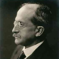 Image: A photographic portrait of a moustachioed man in a suit and wire-rimmed spectacles. He is shown in partial profile