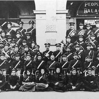 Image: Members of a large band, dressed in dark uniforms with white sashes, pose in lines with their instruments outside of a building with arched doorways.