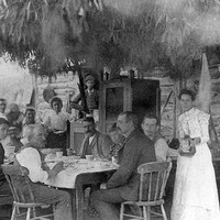 Image: A group of men and women are gathered at a table outside a timber structure. An 'awning' made of plant material is positioned above the table