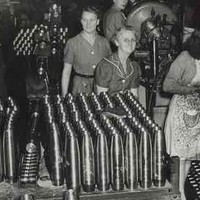 Image: A small group of women stand in a room with several unfinished artillery shells