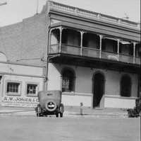 Image: A 1930s-era automobile is parked on a street in front of two buildings. One building is two storeys, made of brick, and has a second-floor verandah