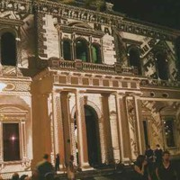 A large, two-storey building at night with images light-projected on its front facade