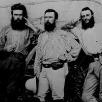Image: four bearded men stand in front of a covered wagon