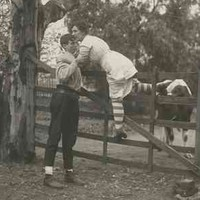 Image: Theatrical still of a young woman in 1920s attire being helped over a high gate by a young man. Behind the gate is a cow, suggesting the woman's narrow escape from danger