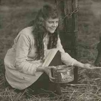 Image: A theatrical still of a young woman squatting beside a tethered calf as she feeds it from a tin. The label on the tin has a brand name for Country Stores, 290 Rundle Street, Adelaide