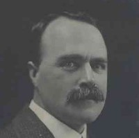 Image: A photographic head-and-shoulders portrait of a moustachioed young man in a suit and tie