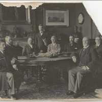 Image: photograph of seven men sitting around a table with an eighth standing behind. The photograph is torn in the top right corner.
