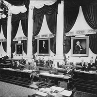 Image: a group of men sit at ornate wooden desks in a room lined with white columns and decorated with portraits, dark coloured curtains and swathes of dark fabric hanging from the ceiling.