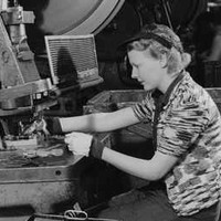 Image: A woman works at a machine to manufacture metal aircraft components