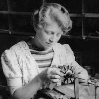 Image: A young woman sits at a table and works on a circular device held in a mounting. The table is covered with several similar devices