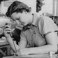 Image: A woman uses a screwdriver to assemble a large metal container. Several similar containers are arrayed in the background